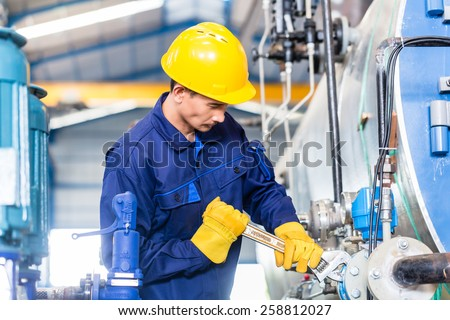 Technician in Asian factory at machine maintenance working with wrench - stock photo