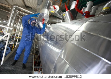 Technician in blue protective  uniform checking technological system - stock photo