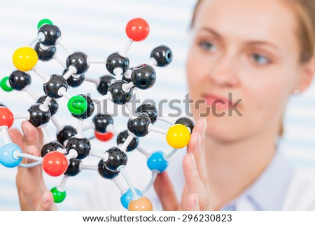 Technician in chemical laboratory with model of molecule - stock photo