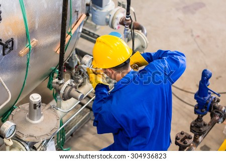 Technician in factory at machine maintenance working with wrench, top view on the man - stock photo