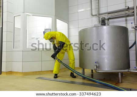 technician in protective coveralls with large hose at industrial tank in plant - stock photo