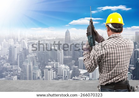 technician in protective safety equipment with drill and tool belt working at high building construction site against blue sky with in concept ecology and real estate