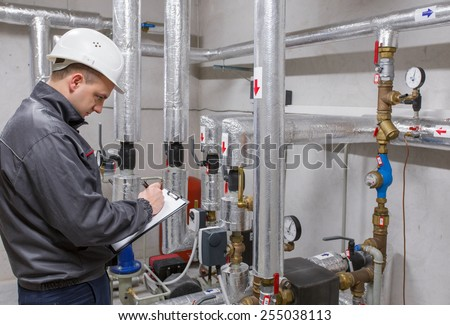 Technician inspecting heating system in boiler room - stock photo