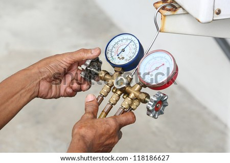 Technician inspection refrigerant pressure of air conditioner - stock photo