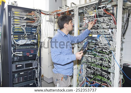 Technician is checking server wires in data center using tablet - stock photo