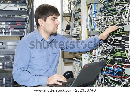 Technician is working with notebook in server's room - stock photo