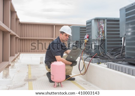 Technician looking at a panel off a condensing unit. - stock photo