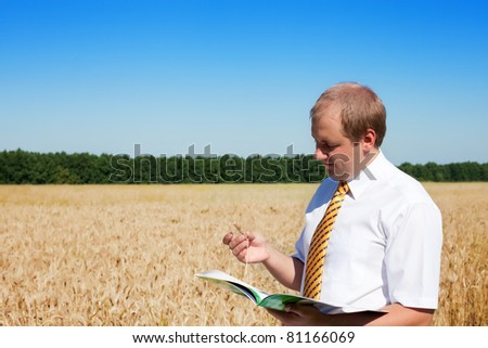 Technician looking at ripe wheat's field during a quality control before the harvest - stock photo