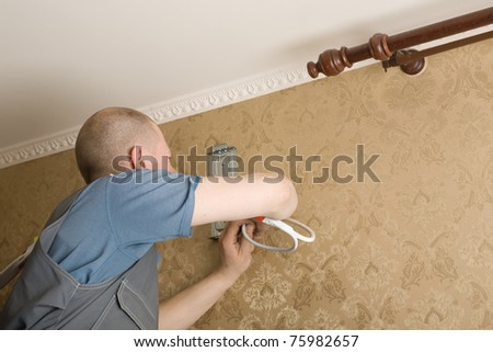 Technician of the air conditioning system is working on installing a new air conditioner in the apartment. - stock photo
