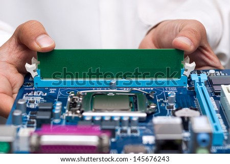 Technician's hands installing user memory on a computer main-board - stock photo