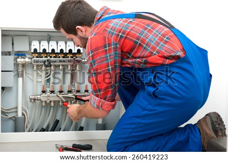 Technician servicing the underfloor heating - stock photo