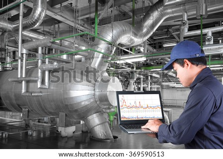 Technician use computer check for maintenance equipment and pipeline in a modern thermal power plant industrial  - stock photo