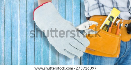 Technician using pliers over white background against wooden planks - stock photo