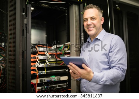Technician using tablet pc while analysing server at the data centre - stock photo