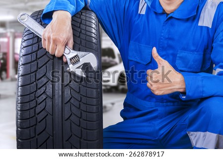 Technician with a blue workwear, holding a wrench and a tire while showing thumb up - stock photo