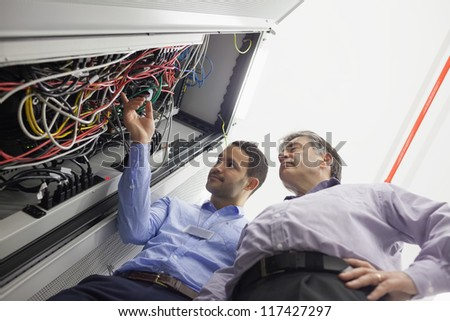 Technicians checking wires of server in data center - stock photo
