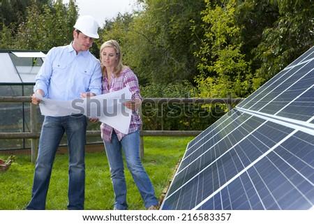 Technicians holding blueprints talking near large solar panels - stock photo