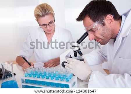Technicians or medical staff in a laboratory working with test tubes in a rack reading samples under the microscope and recording results - stock photo