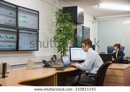 Technicians sitting in office running diagnostics in large data center - stock photo