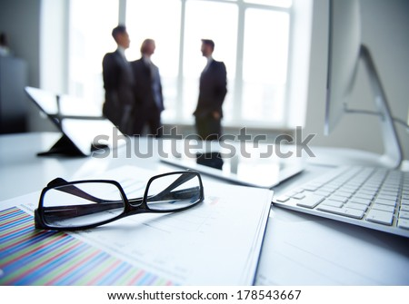 Technological devices, eyeglasses and financial document at workplace on background of three businessmen discussing ideas - stock photo
