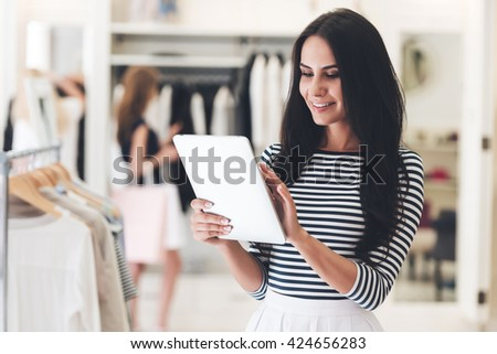 Technologies make business easier. Beautiful young woman using her digital tablet with smile while standing at the clothing store - stock photo