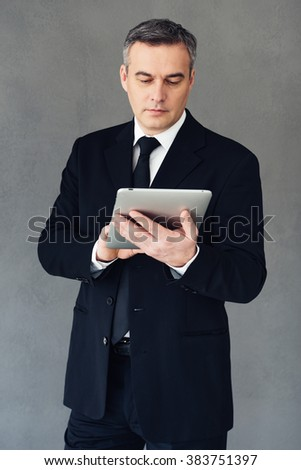 Technologies make business successful. Mature businessman using his touchpad while standing against grey background - stock photo