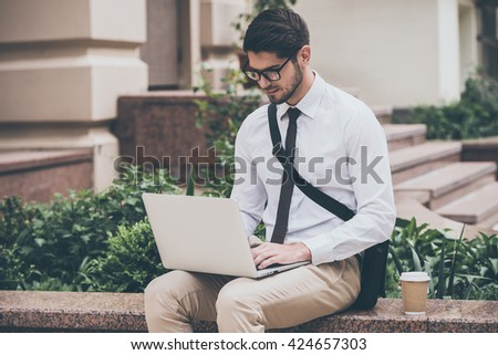 Technologies make life easier. Confident young man in glasses using his laptop while sitting outdoors  - stock photo