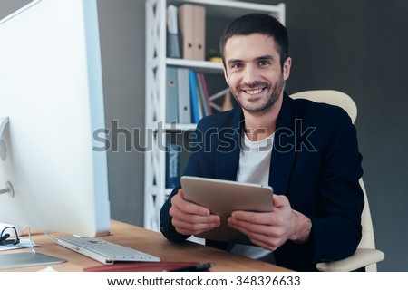 Technologies making life easier. Confident young man holding digital tablet and smiling while sitting at his working place in office - stock photo