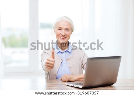 technology, age and people concept - happy senior woman with laptop computer at home showing thumbs up gesture - stock photo