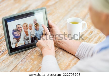 technology, age, memories and people concept - happy senior woman with tablet pc computer viewing family photo album at home - stock photo