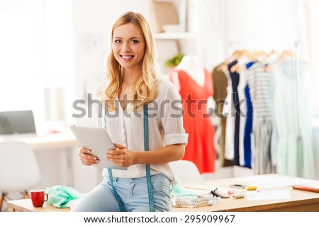 Technology always helps her at work. Happy young woman holding digital tablet and smiling while sitting on the desk in her fashion workshop  - stock photo