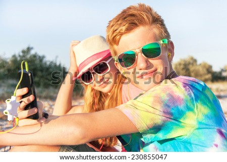 Technology and beach concept. Teenagers (boy and girl) using smart phone and listening music with headphone on the beach. Happy teens are wearing colorful sunglasses and having fun. Summer holidays.  - stock photo