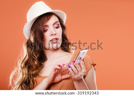 Technology and communication. Attractive summer woman using mobile phone texting on smartphone orange background - stock photo