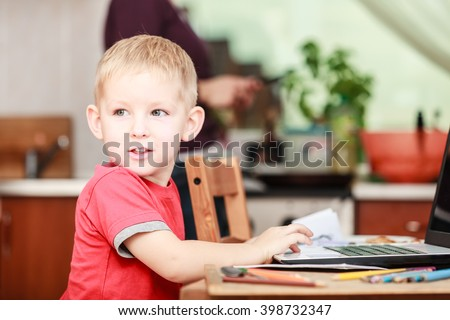 Technology and early education. Child use laptop for fun and learning. Boy sit with computer on table indoors wear red shirt. - stock photo