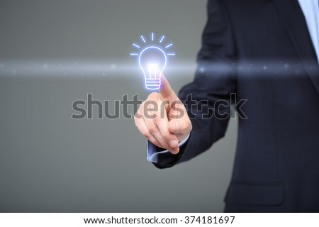 technology and internet concept - businessman pressing button with bulb on virtual screens - stock photo