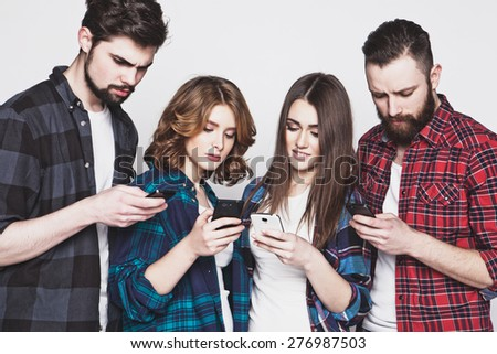 technology and internet concept:group of young people  looking at their smartphones  - stock photo
