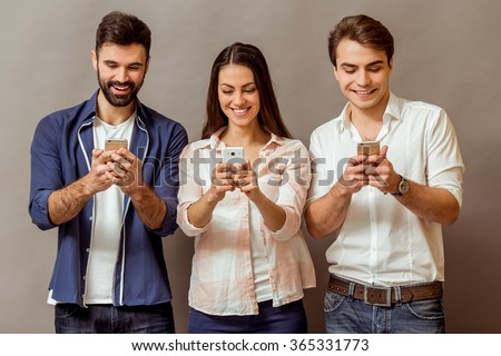 Technology and internet concept: group of young people looking at their smartphones, on a gray background - stock photo