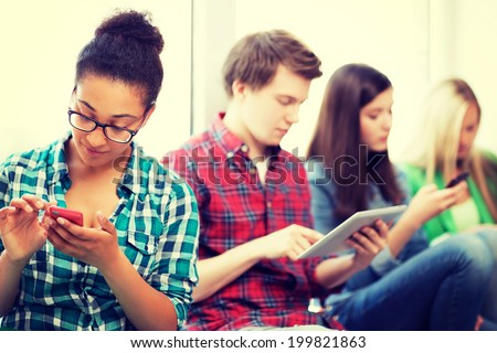 technology and internet concept - students looking into phones and tablet pc at school - stock photo
