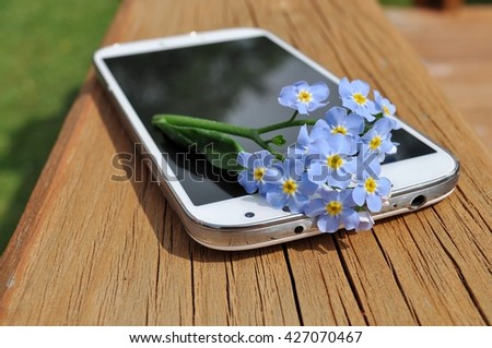 Technology and nature: Smartphone with forget-me-not flower on wooden board. - stock photo