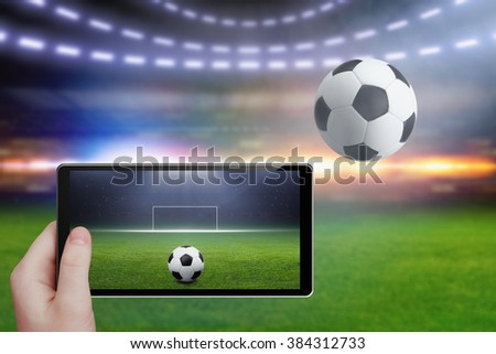 Technology background - tablet pc in hand, soccer ball, stadium in night, sports game online, augmented reality concept - stock photo