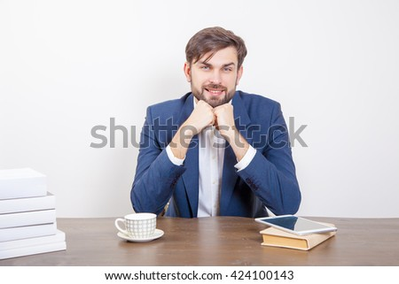 Technology, business concept - handsome man with beard and brown hair and blue suit and tablet pc computer and some books in the office, looking at camera with smile.  Isolated on white background.   - stock photo