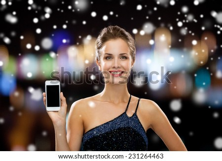 technology, christmas, holidays, advertising and people concept - smiling woman in evening dress holding smartphone over night lights and snow background - stock photo