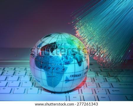 technology earth on laptop keyboard against fiber optic background - stock photo