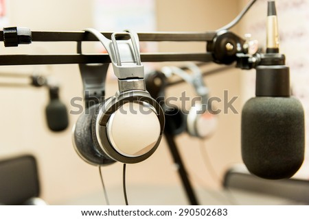technology, electronics and audio equipment concept - close up of headphones and microphone at recording studio or radio station - stock photo