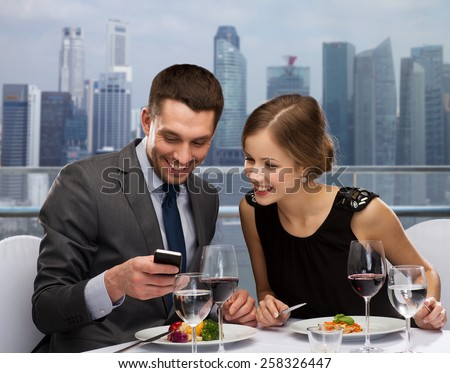 technology, food, holidays and people concept - smiling couple with smartphone eating at restaurant over city background - stock photo