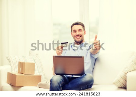 technology, home and lifestyle concept - smiling man with laptop, credit card and cardboard boxes at home showing thumbs up - stock photo