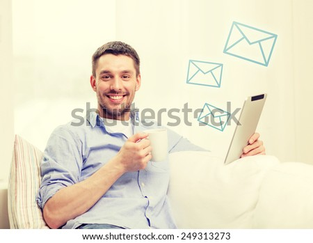 technology, home and lifestyle concept - smiling man working with tablet pc computer and coffee cup at home - stock photo