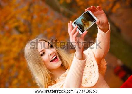 Technology internet and happiness concept. Woman content girl taking self picture selfie with smartphone camera while walking outdoors in autumn park - stock photo