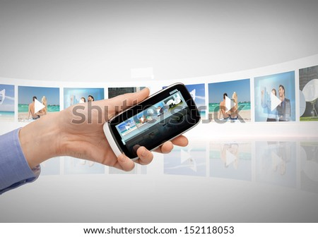 technology, internet, tv and news concept - woman hand with smartphone, videos and virtual screen - stock photo