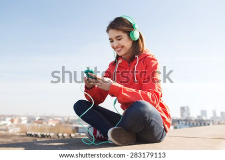 technology, lifestyle and people concept - smiling young woman or teenage girl with smartphone and headphones listening to music outdoors - stock photo